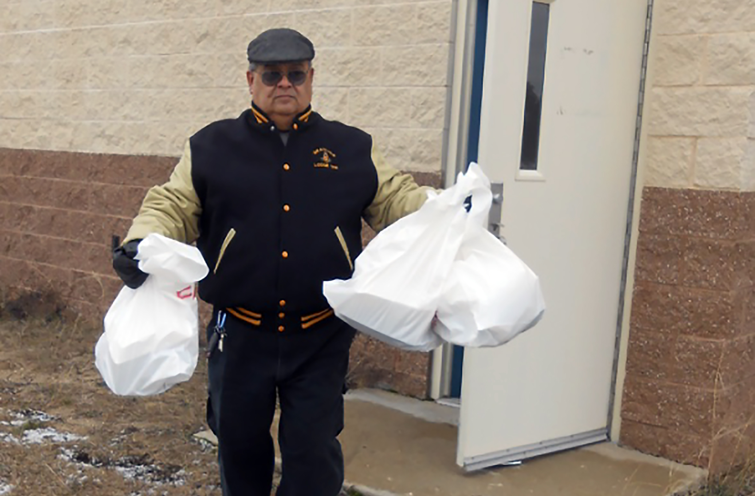 Louis Arreola, a member of the Grayling Masonic Lodge #356, carries a number of meals to waiting vehicles delivering meals.
