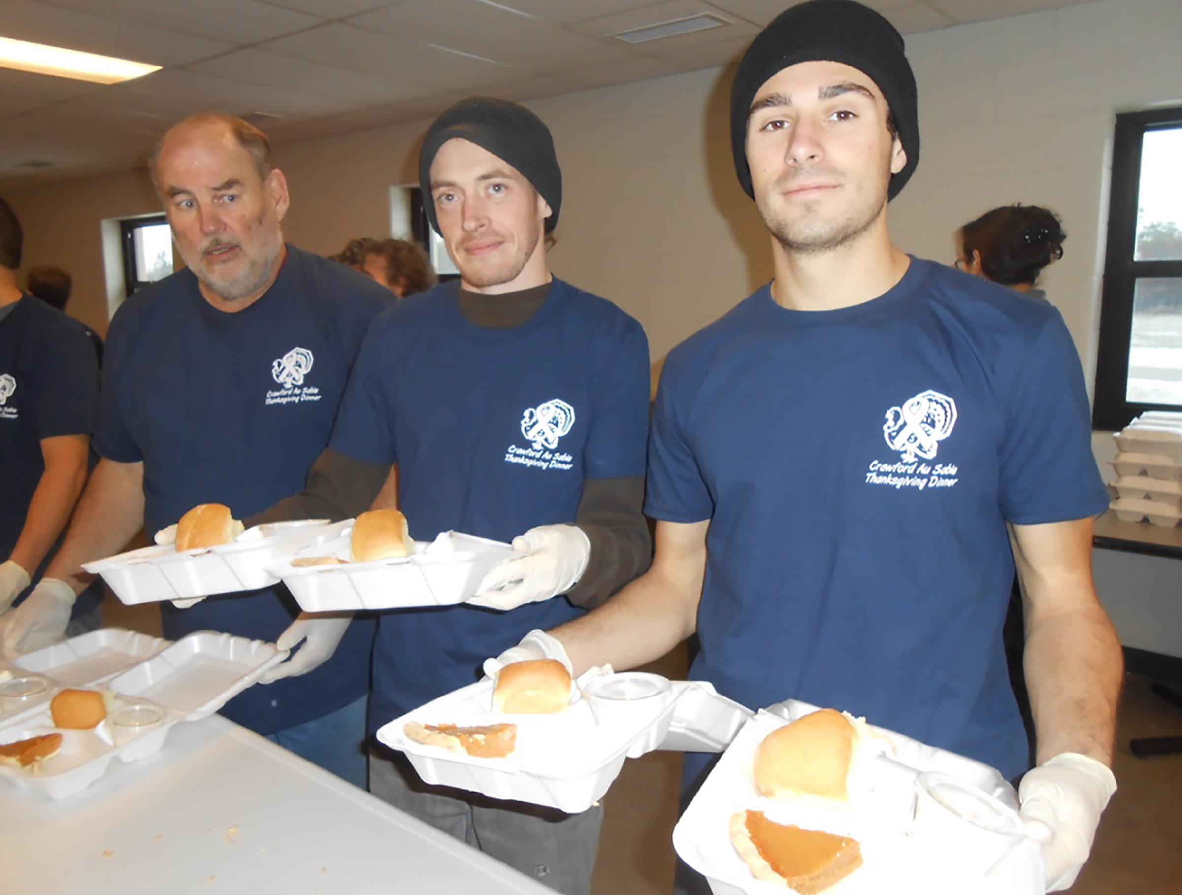 Above, volunteers go through an assembly line as they package meals for deliveries.